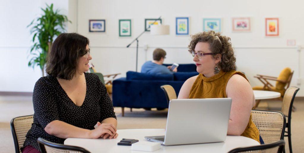 Zwei Mitarbeiterinnen besprechen das korrekte Verhalten im Umgang mit Phishing-Mails